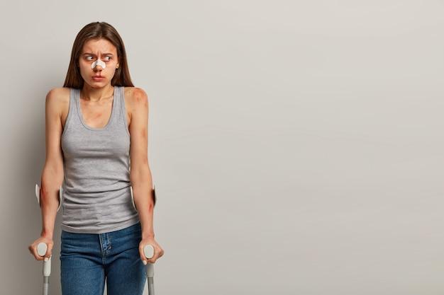 Uitschakelen jonge vrouw bestuurder heeft bloedend gezicht, verband op neus ernstig letsel