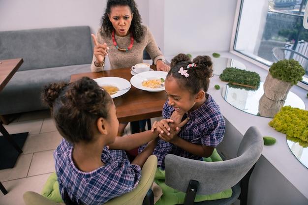 Uitschelden voor gedrag. donkerharige zorgzame moeder die haar kleine meisjes uitscheldt voor slecht gedrag in het restaurant