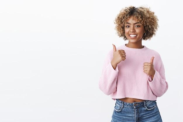 Uitstekend, duimen omhoog voor jou. knappe, ondersteunende en charismatische afro-amerikaanse vriendin met blond afro-kapsel met een leuk en geweldig gebaar als glimlachen, juichen over de witte muur