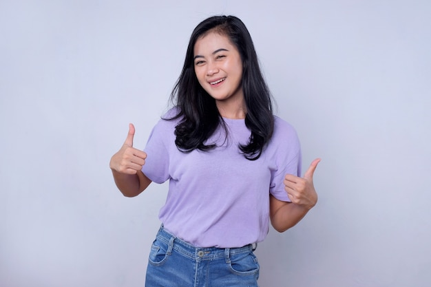 Uitstekend, duimen omhoog voor jou. knappe ondersteunende en charismatische aziatische vrouwelijke vriend met zwart haar die een leuk en geweldig gebaar op een witte muur laat zien
