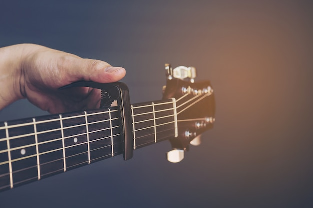 Uitstekend kleurenbeeld van de mens die gitaarcapo over grijze achtergrond zet