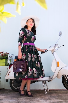 Uitstekend meisje naast motorfiets