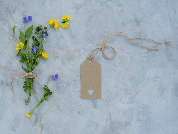 Uitstekend model met de zomerbloemen, een leeg etiket op grijze achtergrond.