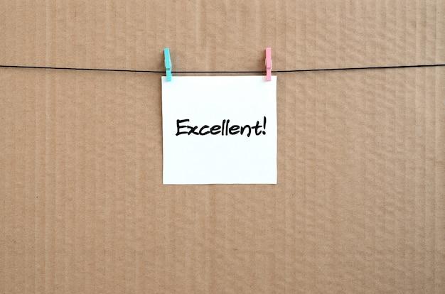 Uitstekend! opmerking staat op een witte sticker die met een wasknijper aan een touw op een achtergrond van bruin karton hangt