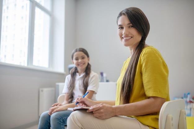 Uitstekend resultaat. vrolijk lachend meisje en jonge langharige vrouw psycholoog zitten in de kamer in de buurt van venster