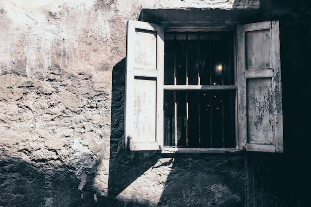Uitstekend toon oud wit houten venster op de rustieke concrete achtergrond van de muurvoorgevel