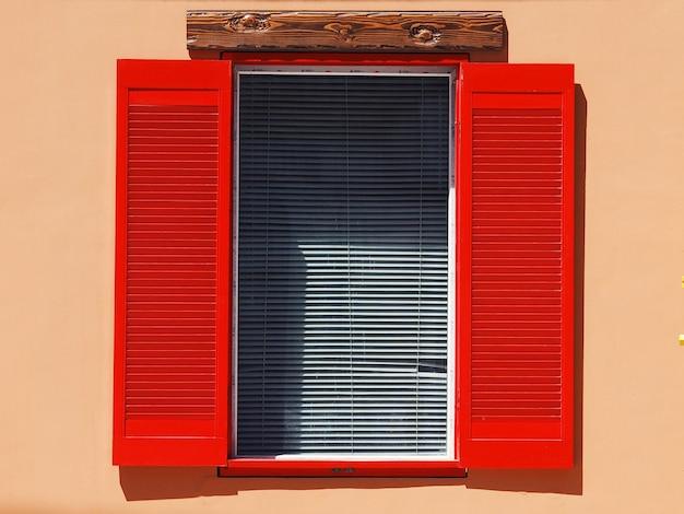 Uitstekend venster op de muur met rode blinden en witte zonneblindenclose-up