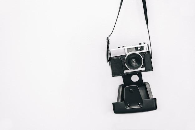 Uitstekende camera die bij witte muur wordt geïsoleerd