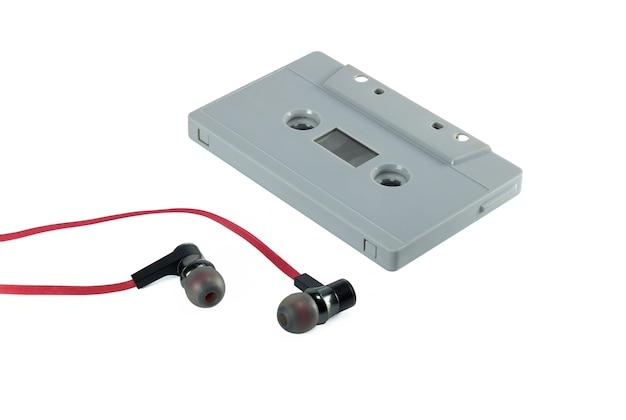 Uitstekende cassetteband en rode die oortelefoon op witte achtergrond wordt geïsoleerd