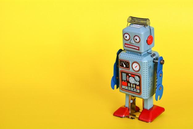 Uitstekende die tinstuk speelgoed robot op een gele achtergrond wordt geïsoleerd