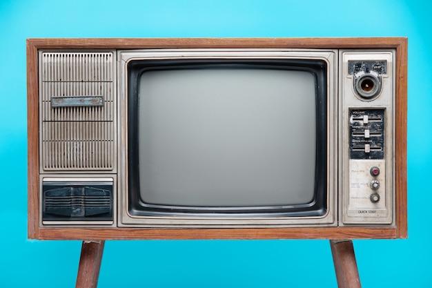 Uitstekende die tv op blauwe achtergrond wordt geïsoleerd.