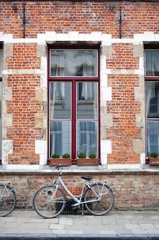 Uitstekende fiets voor oude bakstenen muur en venster