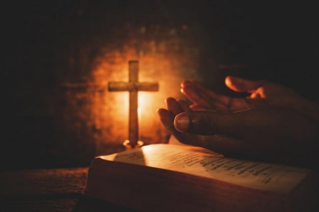 Uitstekende foto van hand met het bidden van de bijbel