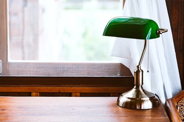 Uitstekende groene lamp op lijst met venster in dagtijd
