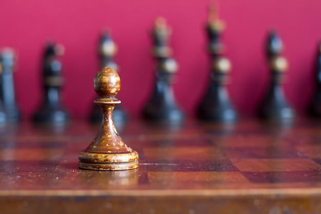 Uitstekende houten schaakstukken op een oud schaakbord, selectieve nadruk.
