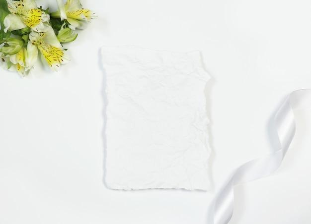 Uitstekende kaart met bloemen en lint op witte achtergrond