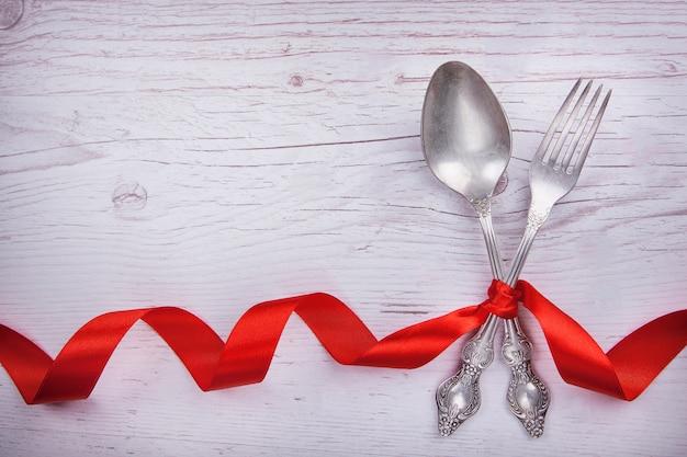 Uitstekende lepel en vork met bureaucratische formaliteiten voor de dag van valentine op een houten lijst.