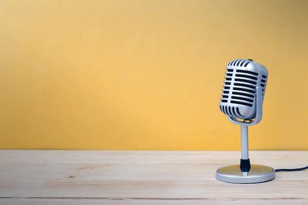 Uitstekende microfoon die op houten en gele achtergrond wordt geïsoleerd