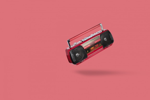 Uitstekende radiocassetterecorder die over roze achtergrond wordt geïsoleerd