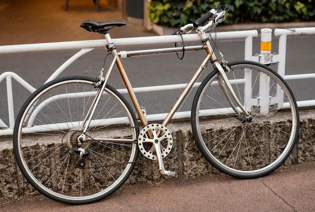 Uitstekende roestige fiets dichtbij omheining