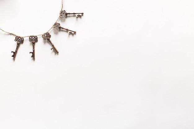Uitstekende sleutels die op witte achtergrond hangen