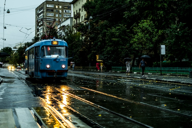 Uitstekende stadstram die zich in de straat tijdens de regen in de avond beweegt
