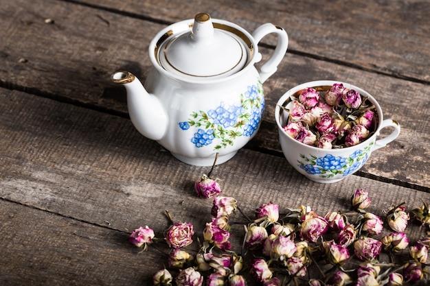 Uitstekende theepot en kop met bloeiende theebloemen op hout