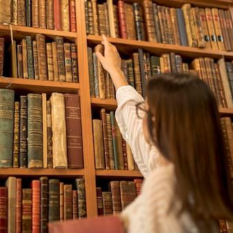 Uitstekende vrouwelijke student die uitstekend boek in bibliotheek kiest