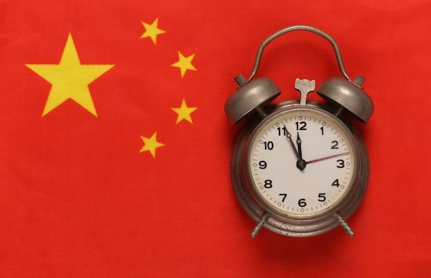 Uitstekende wekker op achtergrond van de vlag van china china