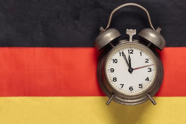 Uitstekende wekker op achtergrond van de vlag van duitsland germany