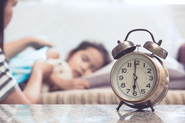 Uitstekende wekker op achtergrond van moeder die aziatisch kindmeisje nemen terwijl zij die in het bed slapen