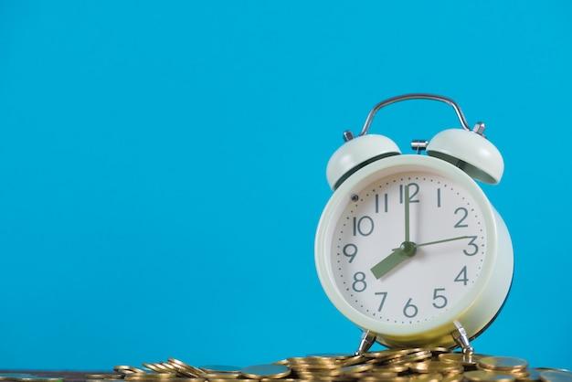 Uitstekende wekker op de stapel van gouden muntstuk met blauwe achtergrond