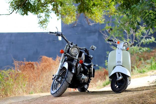 Uitstekende zwarte motorfiets die zich dichtbij witte motor in stralen van zonlicht bevindt. zijaanzicht