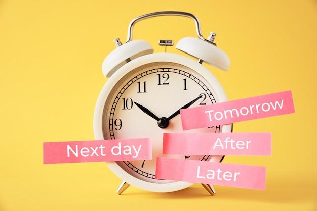 Uitstel, vertraging en concept uitstellen. wekker met plaknotities later, morgen, de volgende dag en daarna
