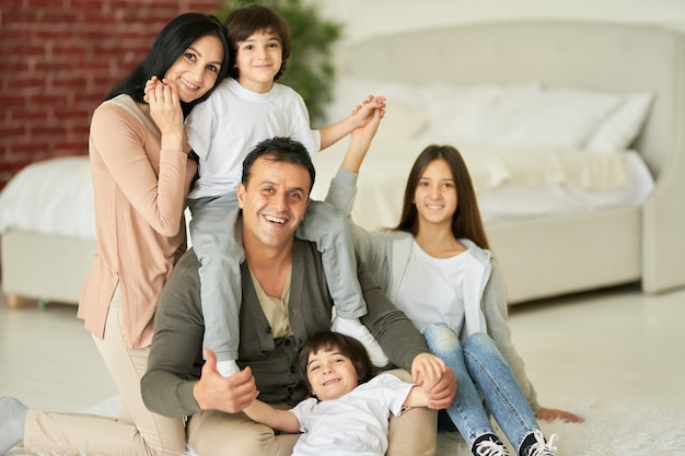 Uitstralend geluksportret van latijnse familie tienerdochter en kleine jongens die naar de camera glimlachen