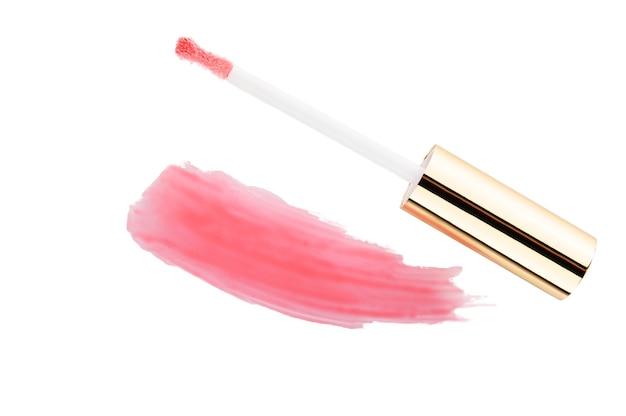 Uitstrijkje van roze lipgloss en penseel op een wit