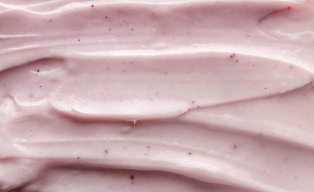 Uitstrijkjes van roze cosmetische crème. schoonheid crème textuur achtergrond.