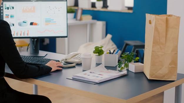 Uitvoerend manager met papieren zak met afhaalmaaltijden lunchbestelling op bureau zetten tijdens afhaall...