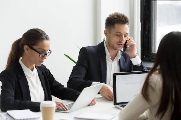 Uitvoerende bedrijfsmensen die laptops voor het werk met behulp van, die op telefoon spreken