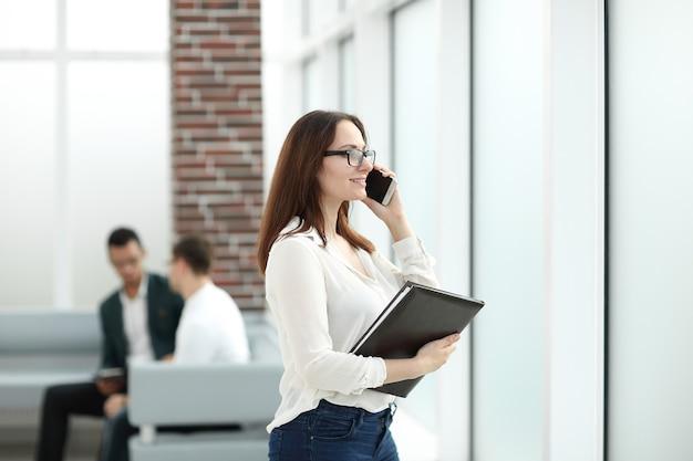 Uitvoerende bedrijfsvrouw die met klembord op mobiele telefoon spreekt.