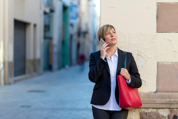 Uitvoerende die op telefoon spreken die zich op de straat bevinden