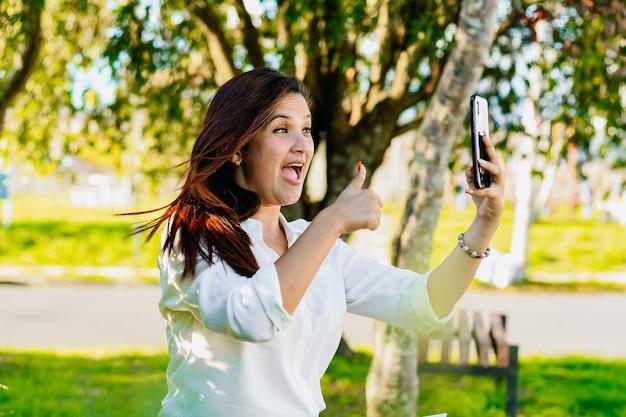 Uitvoerende vrouw die een videogesprek voert, zittend in het park. met haar hand een teken van alles goed maken