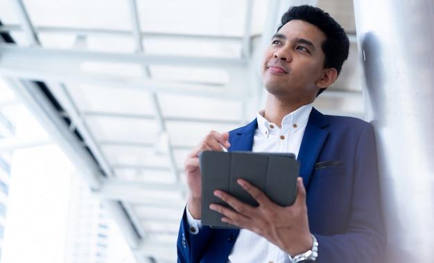 Uitvoerende zakenman hand met tablet en touchscreen aan het controleren van het werk