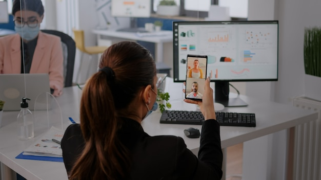 Uitvoerende zakenvrouw die een beschermend gezichtsmasker draagt met behulp van de telefoon voor een online videogesprekconferentie met een team op afstand. collega's die op de achtergrond werken en de sociale afstand respecteren