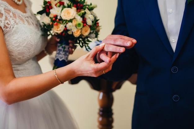 Uitwisseling van gouden ringen van de bruid en bruidegom op de bruiloft