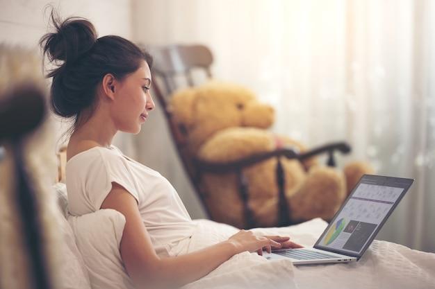 Uitwisselingsstudent of zakenvrouw werkt vanuit of thuis concept voor sociale afstand nemen tijdens covid pandemie met een informele levensstijl op comfortabel bed