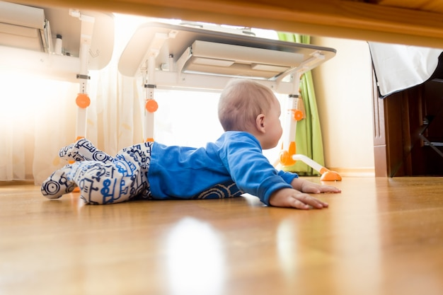 Uitzicht onder het bed op schattige baby die op de vloer kruipt in de slaapkamer