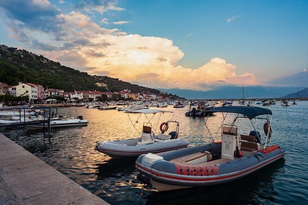 Uitzicht op afgemeerde boten bij zonsondergang in de stad baska, krk. kroatië
