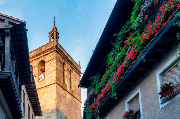 Uitzicht op balkon met bloemen en de versterkte toren van de kerk van la alberca in salamanca, spanje.