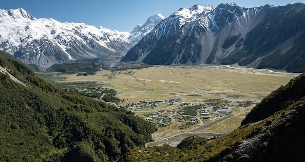 Uitzicht op bergdorp gelegen in de vallei en omgeven door hoge toppen geschoten op nieuw-zeeland